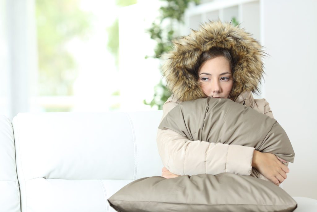 Woman warmly clothed in a cold home | colorado springs hvac service