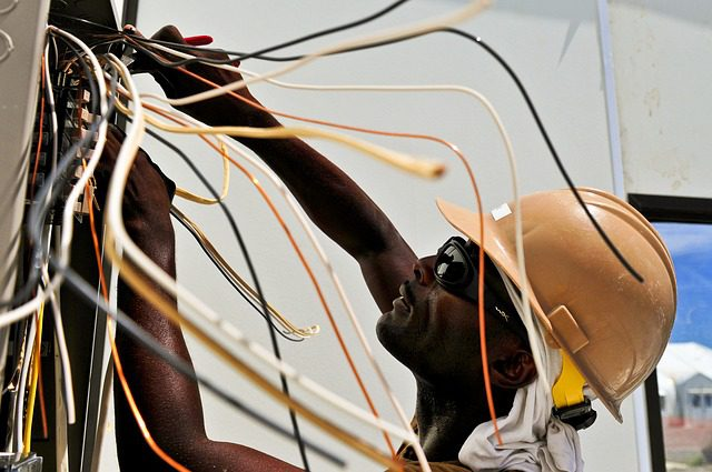 a technician fixes wires in a wall | colorado springs electrician