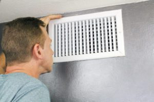 a man looks into his ducts needing duct sealing in colorado springs