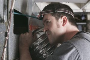 a man searching for duct leaks in colorado springs