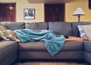person laying on couch with blanket